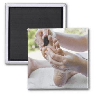Woman getting foot massage with hot stone square magnet