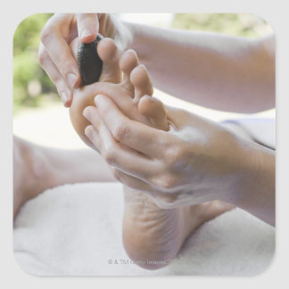 Woman getting foot massage with hot stone square sticker