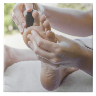 Woman getting foot massage with hot stone tile