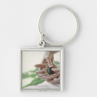 Woman getting hand massage with hot stone key ring