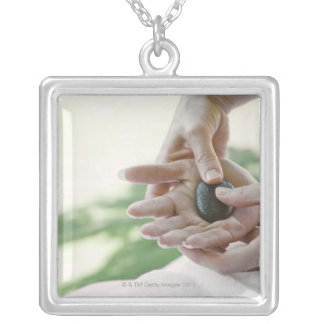 Woman getting hand massage with hot stone silver plated necklace
