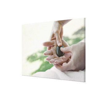 Woman getting hand massage with hot stone stretched canvas print
