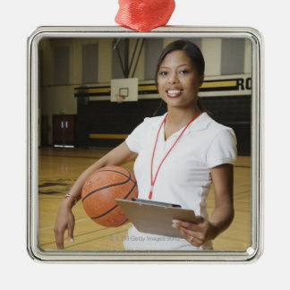 Woman holding basketball and clipbpard, smiling, christmas ornament
