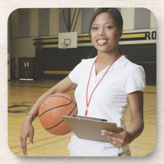 Woman holding basketball and clipbpard, smiling, coaster