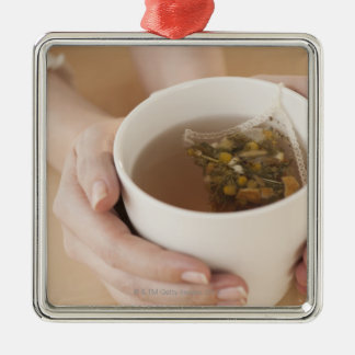 Woman holding cup with chamomile tea christmas ornament