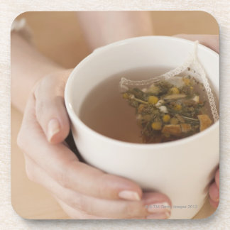 Woman holding cup with chamomile tea coaster