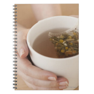 Woman holding cup with chamomile tea notebooks