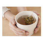 Woman holding cup with chamomile tea post card