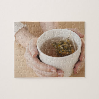Woman holding cup with chamomile tea puzzle