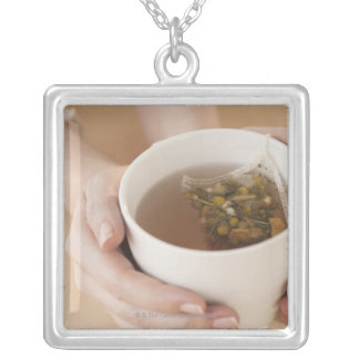 Woman holding cup with chamomile tea silver plated necklace