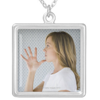 Woman holding open hand to chin. square pendant necklace