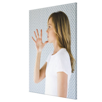 Woman holding open hand to chin. stretched canvas prints