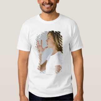 Woman holding open hand to chin. t shirt