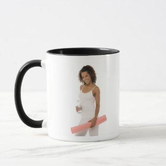 Woman holding water bottle and exercise mat mug