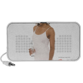 Woman holding water bottle and exercise mat travel speakers