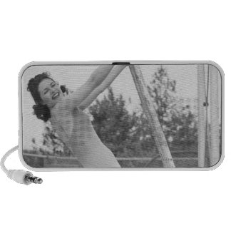 Woman in swimsuit hanging from wooden travelling speakers