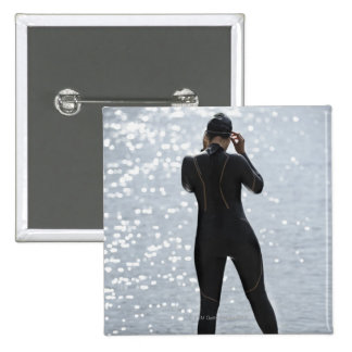 Woman in wetsuit standing on rock 15 cm square badge