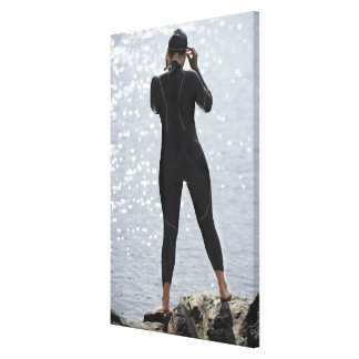 Woman in wetsuit standing on rock canvas print