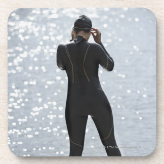 Woman in wetsuit standing on rock coaster
