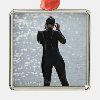 Woman in wetsuit standing on rock christmas tree ornaments