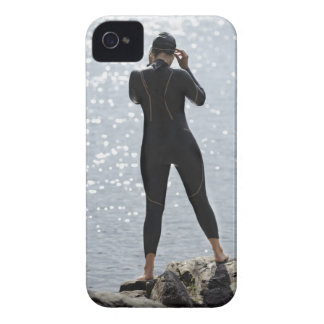 Woman in wetsuit standing on rock iPhone 4 cases