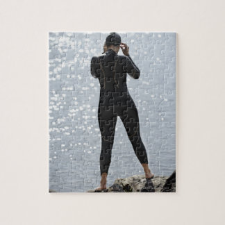 Woman in wetsuit standing on rock jigsaw puzzle