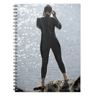 Woman in wetsuit standing on rock notebook