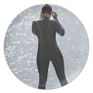Woman in wetsuit standing on rock plate