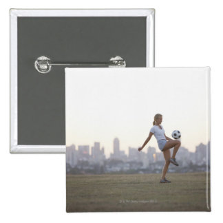 Woman kneeing soccer ball in urban park 15 cm square badge
