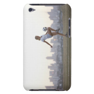 Woman kneeing soccer ball in urban park iPod touch case