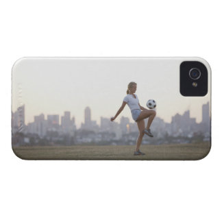 Woman kneeing soccer ball in urban park iPhone 4 case