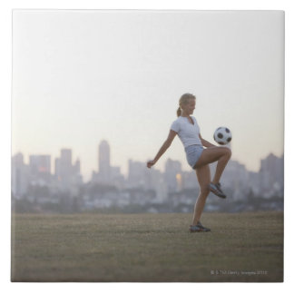 Woman kneeing soccer ball in urban park large square tile