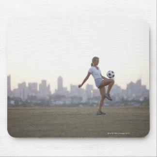 Woman kneeing soccer ball in urban park mouse pads