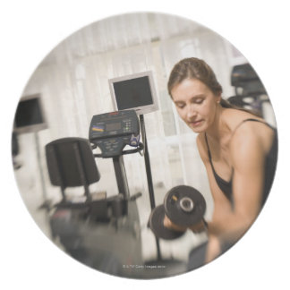 Woman lifting weights in gym 2 party plate
