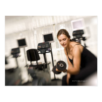 Woman lifting weights in gym 2 postcard