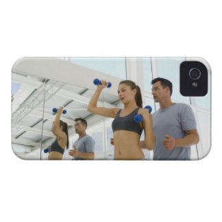 Woman lifting weights with trainer iPhone 4 covers