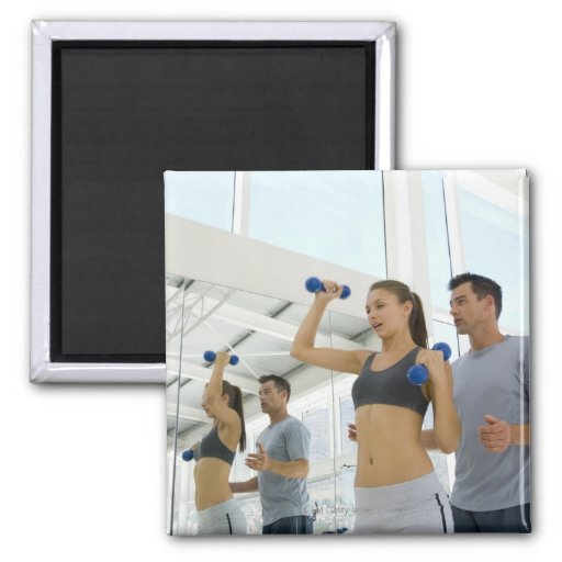Woman lifting weights with trainer refrigerator magnet