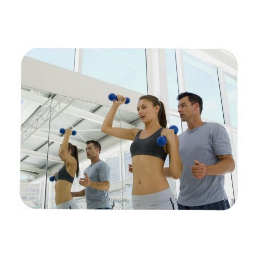 Woman lifting weights with trainer vinyl magnet