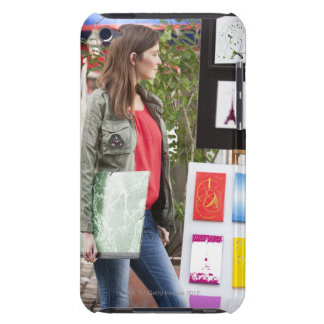 Woman looking at postcards of Eiffel Tower at a iPod Touch Cover