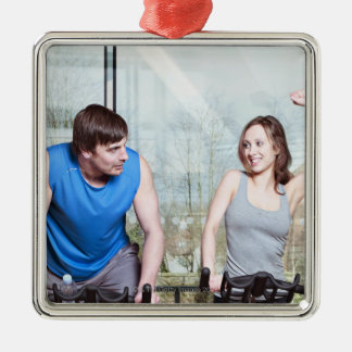 Woman on exercise bike triumphing over man christmas ornament