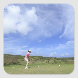 Woman playing golf square sticker