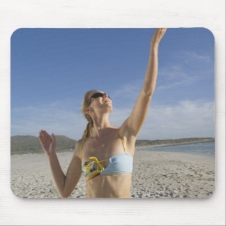 Woman playing volleyball on beach mouse mat