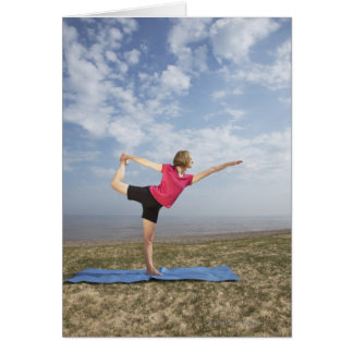 Woman practicing yoga by the beach card