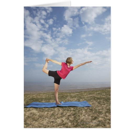 Woman practicing yoga by the beach cards