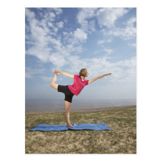 Woman practicing yoga by the beach postcard