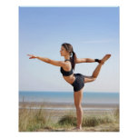 Woman practicing yoga on beach poster