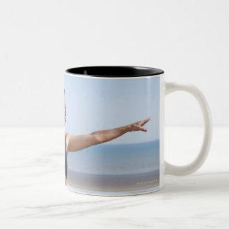 woman practicing yoga on beach wearing Two-Tone coffee mug