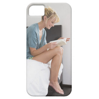 Woman reading a book on the bed case for the iPhone 5