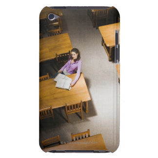 Woman reading book in library iPod touch cases