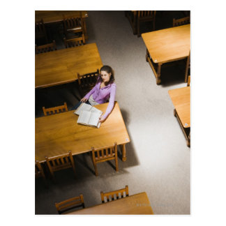 Woman reading book in library post card